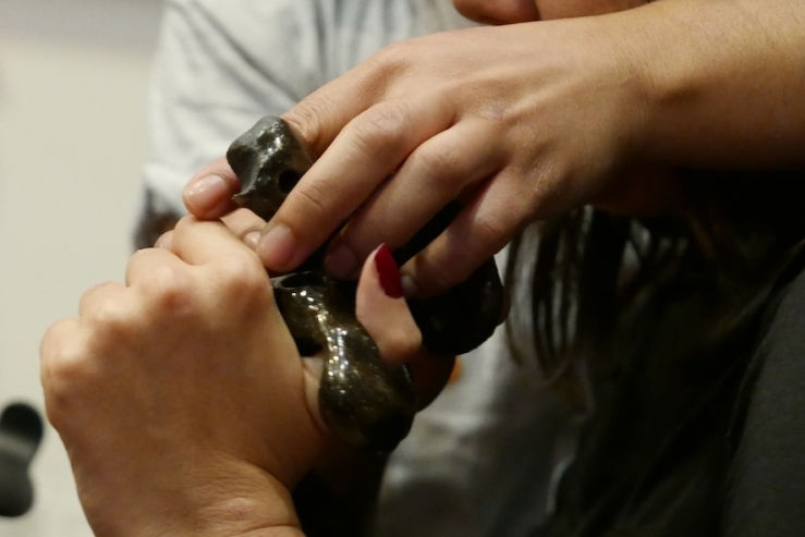 Image shows a close up on two hands gripping a strange ceramic tool which is black and shiny. One of the hands has deep red nail polish. The hands are knotted around the tool. You cannot see who they belong to.