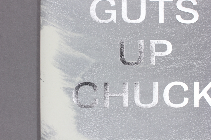 A close crop of part of the front cover of publication Guts Up Chuck, showing the title in metalic silver against a brushed, washed out grey. The background beneath the publication is dark grey.