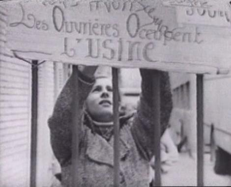 A black and white photograph of a white woman behind the bars of a gate. She is reaching up to attach a hand-painted banner that reads: Les Ouvrieres Occupent L'usine [translation: workers occupy the factory].