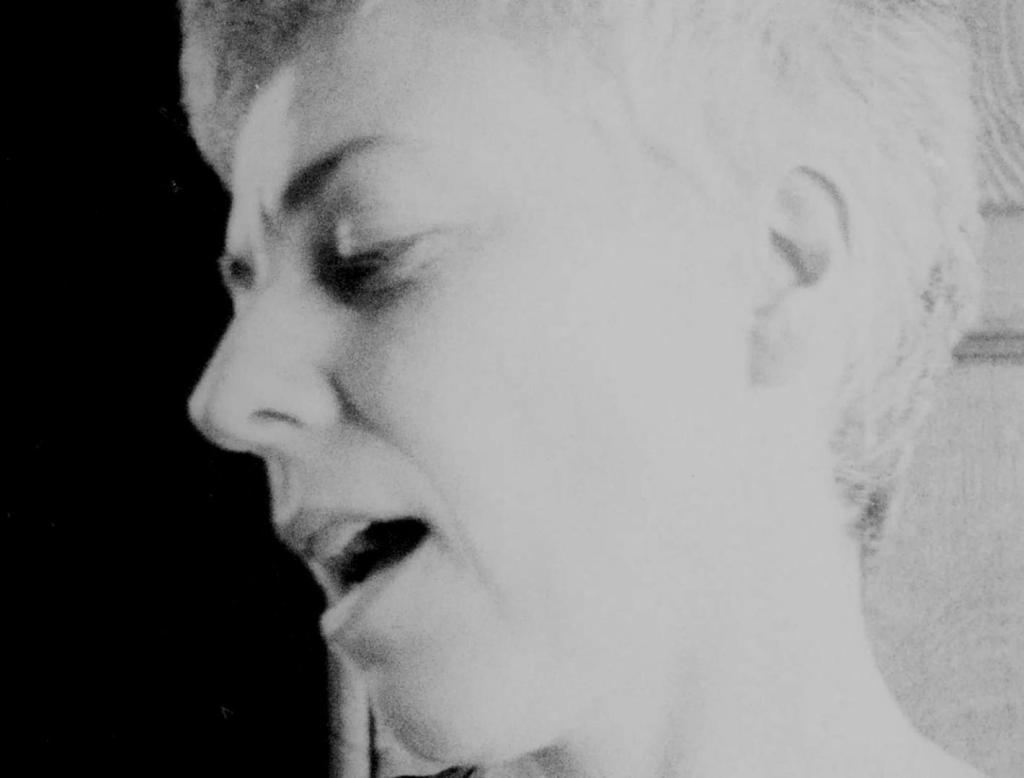 A black and white film still of a white woman with short hair in front of a black background. She is shown in profile and the image is cropped in close, filling most of the frame.